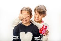 Little girl giving surprise love gift to her friend with white b Stock Image