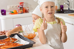 Little girl giving a thumbs up as she bakes pizza Royalty Free Stock Images