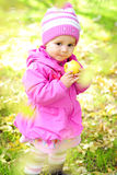 The little girl on a glade with an apple. The little girl on a green glade with an apple Royalty Free Stock Photo