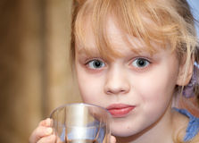 Little girl with a glass in her hand Royalty Free Stock Photo