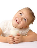 Little girl with a glass of milk looks up Stock Photography