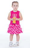 Little girl with a glass of orange juice. Stock Photos