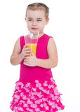 Little girl with a glass of orange juice. Royalty Free Stock Images