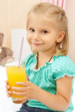 Little girl with glass of orange juice Stock Image