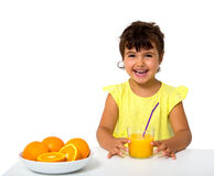 Little girl with glass of orange juice Royalty Free Stock Photos
