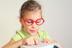Little girl in glass put finger on text. In book, read Royalty Free Stock Image