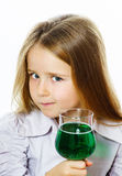 Little girl with glass of vivid green liquid, maybe poison Royalty Free Stock Photo