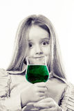 Little girl with glass of vivid green liquid, maybe poison Stock Images
