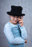 Little girl in glasses and black hat. Looking at camera and smiling in front of grey background Stock Photography