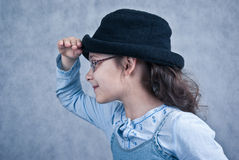 Little girl in glasses and black hat profile. Little girl in glasses and black hat looking and smiling in front of grey background - profile Royalty Free Stock Image
