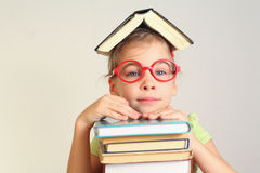 Little girl in glasses with book on head. Hands on books Royalty Free Stock Images