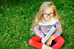 Little girl in glasses with book outdoors stock photo