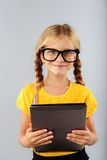 Little girl in glasses  on grey background Stock Images