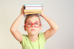 Little girl in glasses hold books. On head Royalty Free Stock Images