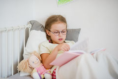 Little girl with glasses leafing through a book while lying in bed. Royalty Free Stock Photo