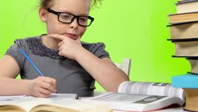 Little girl in glasses looking in books information. Green screen stock footage