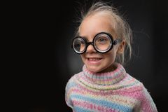 Little girl in glasses makes faces Stock Images