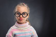 Little girl in glasses makes faces Royalty Free Stock Images