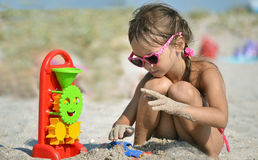 Little girl with glasses plays with sand Stock Photo
