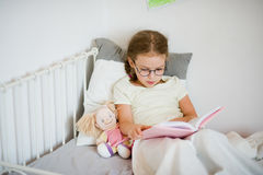 Little girl in glasses reading a book while lying in bed. Stock Images