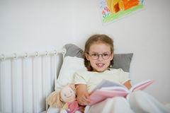Little girl in glasses reading a book while lying in bed. Royalty Free Stock Photos