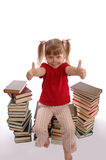 The little girl in glasses sits on books. On a white background Stock Photo