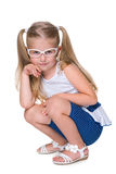 Little girl in glasses sits on the floor Royalty Free Stock Photo