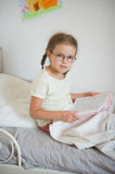 Little girl with glasses sitting in bed and holding an open book. Royalty Free Stock Photo
