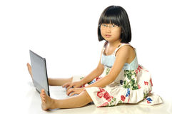 Little girl in glasses sitting on floor using a laptop, white ba Royalty Free Stock Photos