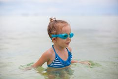 Little girl with glasses for swimming swims and Stock Photo