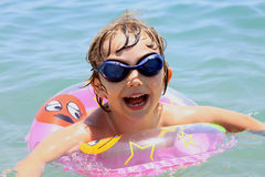 Little girl with glasses swims in the sea Royalty Free Stock Photo