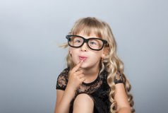 Little girl in glasses thinking Royalty Free Stock Images