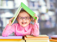 Little girl in glasses under book roof or house stock images