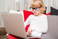 Little girl with glasses using modern technology. Little girl with glasses using  technology Royalty Free Stock Image