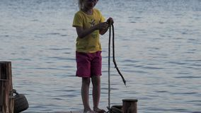 A little girl in glasses and in yellow T-shirt is having fun on the wooden pier. The girlis wetting her feet in the water, running stock video
