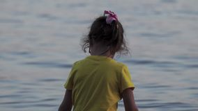 A little girl in glasses and in yellow T-shirt is having fun on the wooden pier. The girlis wetting her feet in the water, running stock video footage