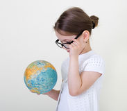 The little girl  and globe. The little girl studying a globe Royalty Free Stock Photos