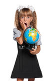 Little girl with globe. Little girl in school uniform with globe of the world isolated on white background Royalty Free Stock Photo