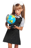 Little girl with globe. Little girl in school uniform with globe of the world isolated on white background Royalty Free Stock Images