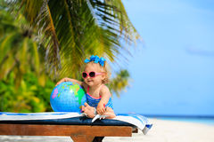 Little girl with globe and toy plane on beach Stock Photos