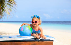 Little girl with globe and toy plane on beach. Kids travel Stock Image