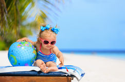 Little girl with globe and toy plane on beach Royalty Free Stock Images