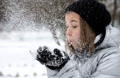 Little girl in gloves and hat blowing snow on park Royalty Free Stock Images