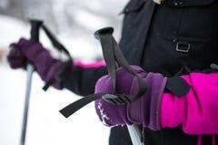 Little girl in gloves holding ski sticks Stock Photos