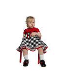 Little girl glutton. Little girl and she ate sitting on a red chair and children's rest stock images