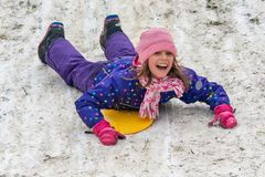 The little girl goes down the snow on the stomach stock photos