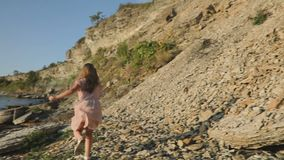 A little girl goes down the stony slope and runs along the sea coast. stock footage