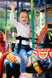 Little girl goes for a drive on carousel. Photo of little girl goes for a drive on carousel Royalty Free Stock Photos