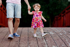 Little girl goes in hand with dad on bridge Stock Images