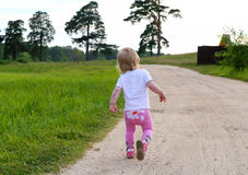 Little girl goes on the sandy road. Little girl goes on the sandy road alone Royalty Free Stock Image